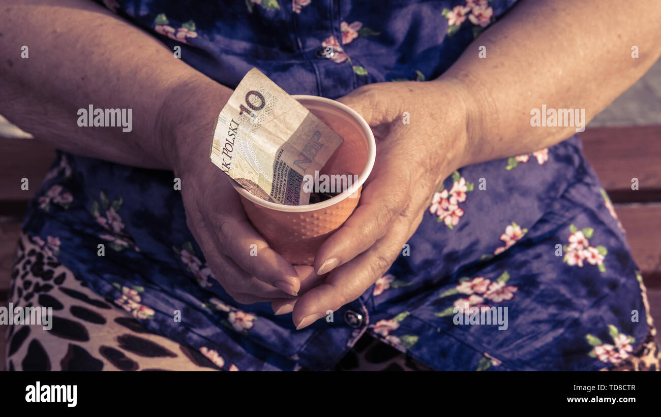 Old woman begs for alms. Closeup of money and coins in hand of poor woman. Social problems of society - Stock Image