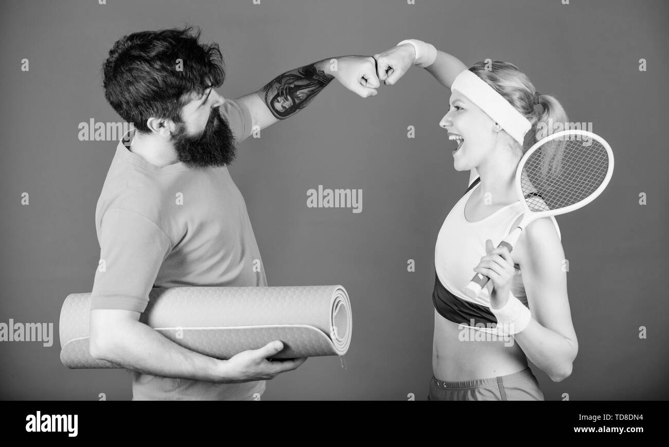 support of Happy woman and bearded man workout in gym. Strong muscles and body. Sport equipment. Sporty couple training with fitness mat and tennis ra - Stock Image
