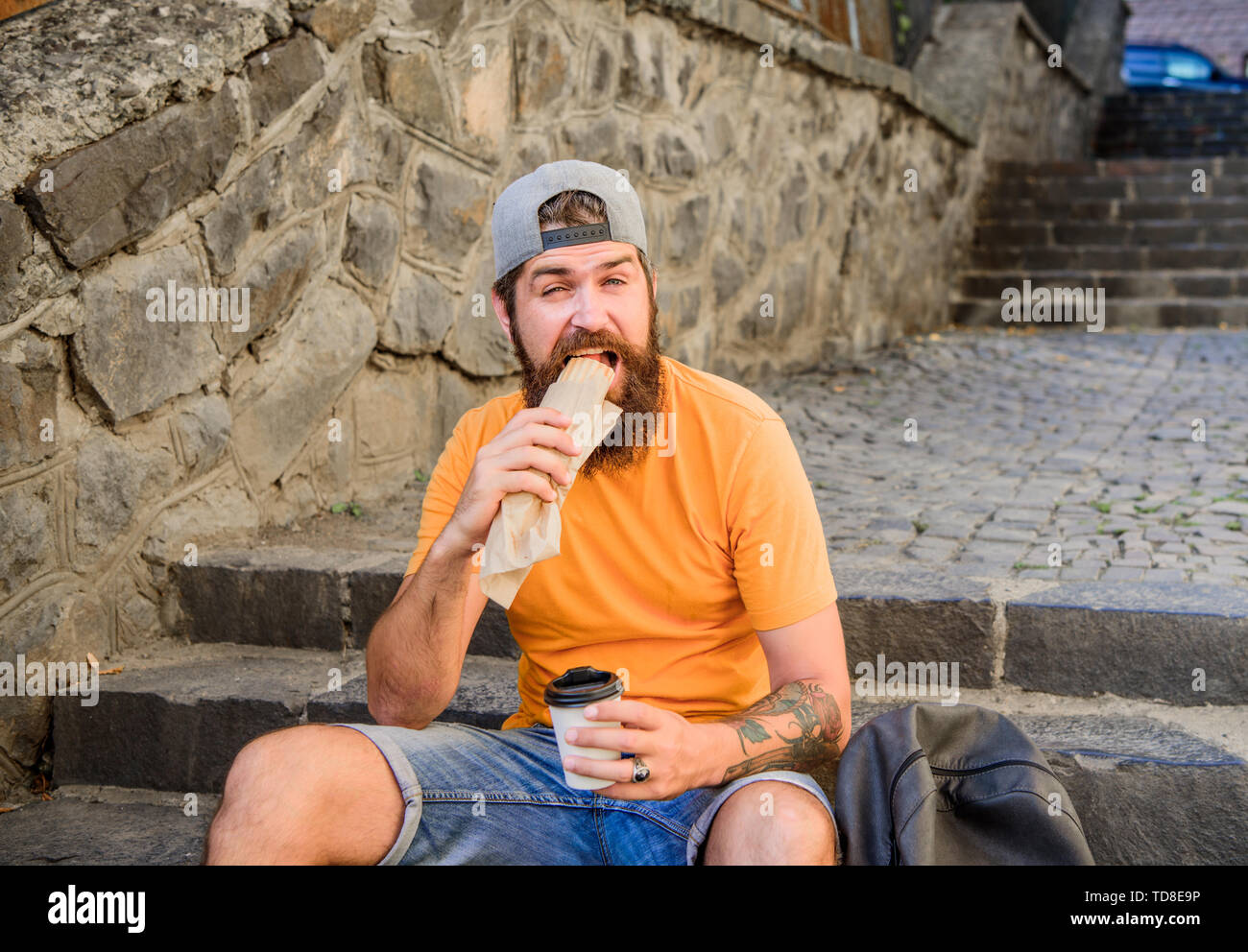 Street food so good. Urban lifestyle nutrition. Carefree hipster eat junk food while sit on stairs. Hungry man snack. Junk food. Guy eating hot dog. Man bearded enjoy quick snack and drink paper cup. - Stock Image