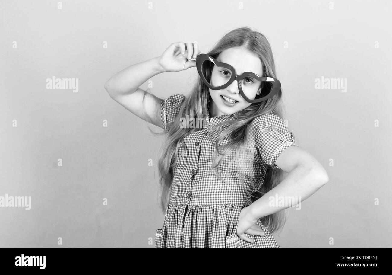 Fashion eyewear. Kid girl heart shaped eyeglasses. Girl adorable smiling face fall in love. Child charming smile blue background. Kid happy lovely enjoy childhood. Heart symbol of love. Power of love. Stock Photo