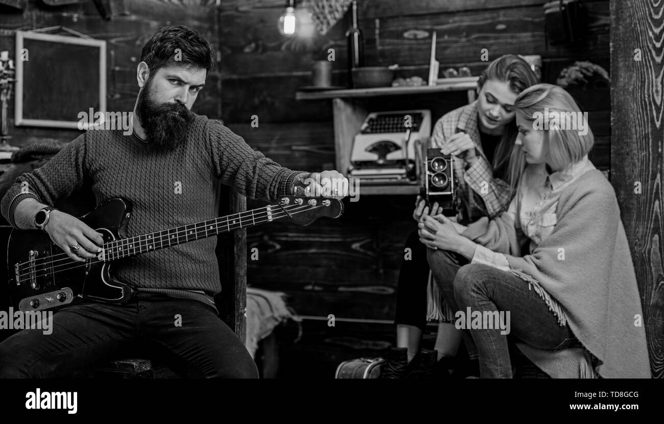 Mom and teenage girl recording musical performance on video camera. Rock musician caressing favorite instrument. Bearded man with brutal look playing  - Stock Image