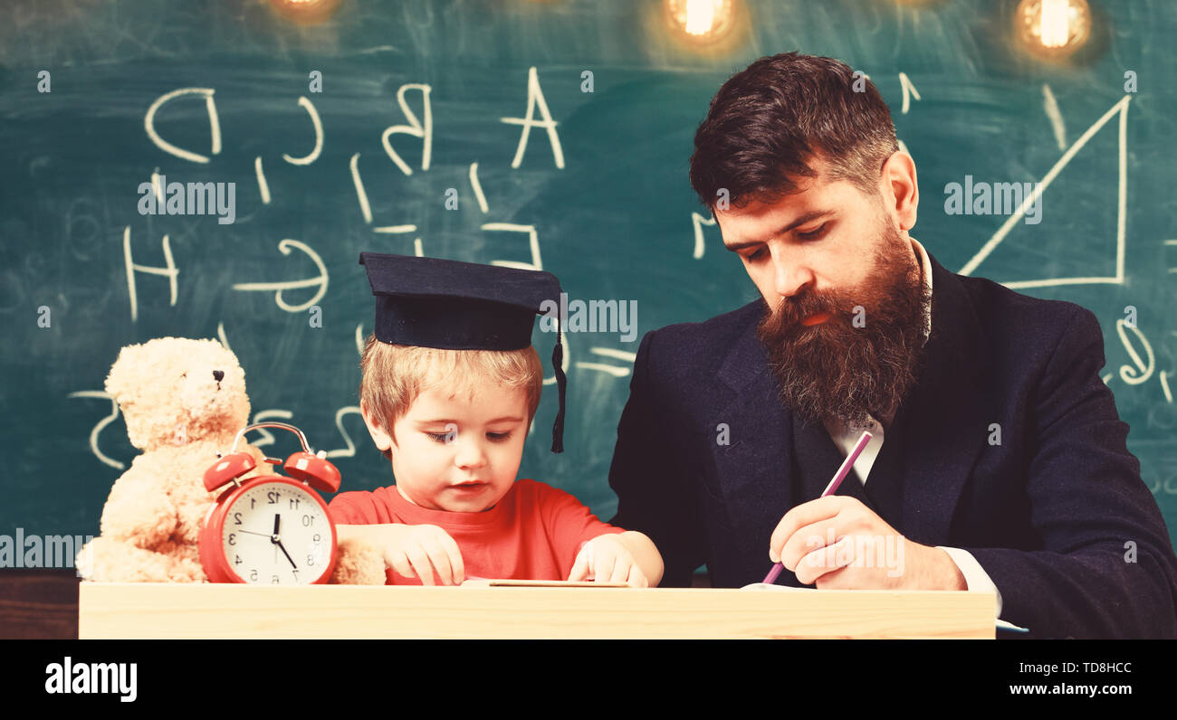 Teacher in formal wear and pupil in mortarboard in classroom, chalkboard on background. Father checking homework, helps to boy, son. Homeschooling concept. Enthusiastic kid studying with teacher. - Stock Image