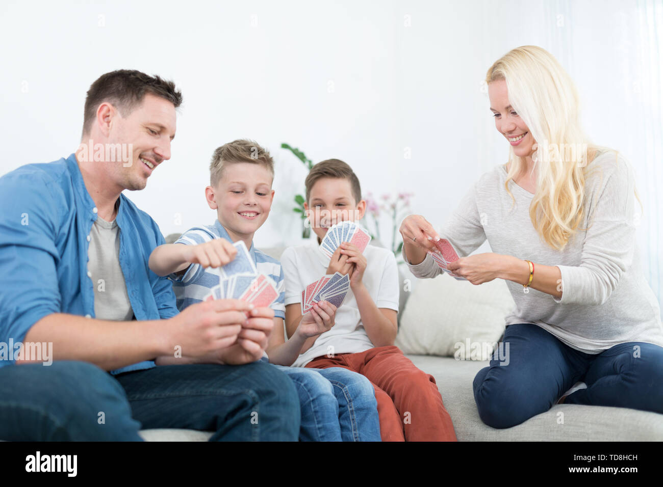 Happy young family playing card game at home. - Stock Image