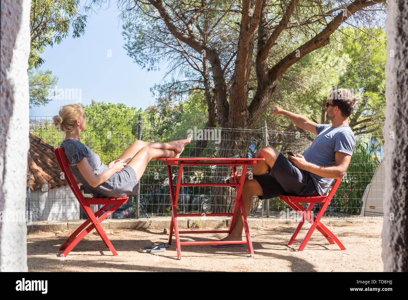 Couple on vacations resting in front of bungalow house at camping site in pure nature. Family vacation travel, holiday trip Sardigna, Italy - Stock Image
