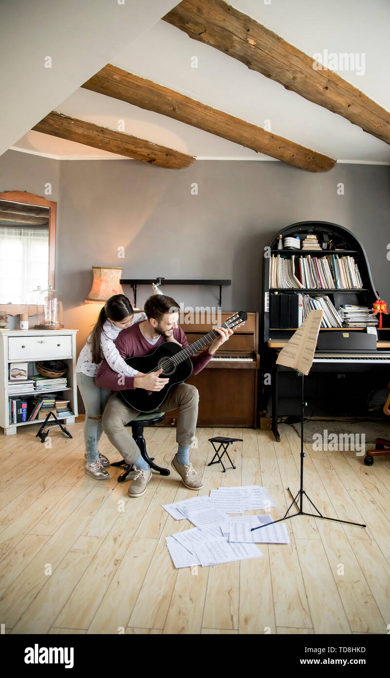 Cute little girl and her handsome father are playing guitar and smiling while sitting  at home - Stock Image