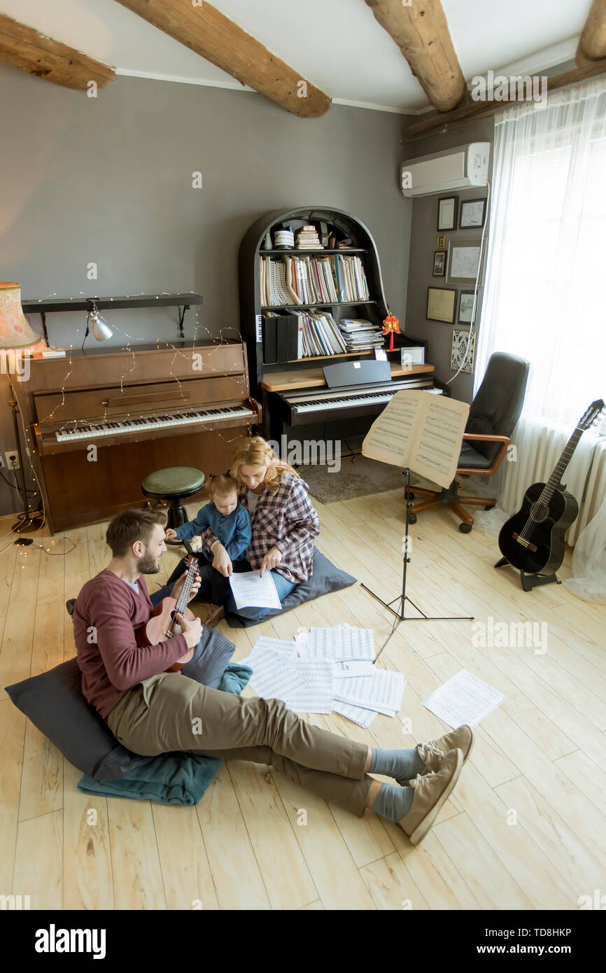 Happy family having fun time at home playing on the floor in the room - Stock Image