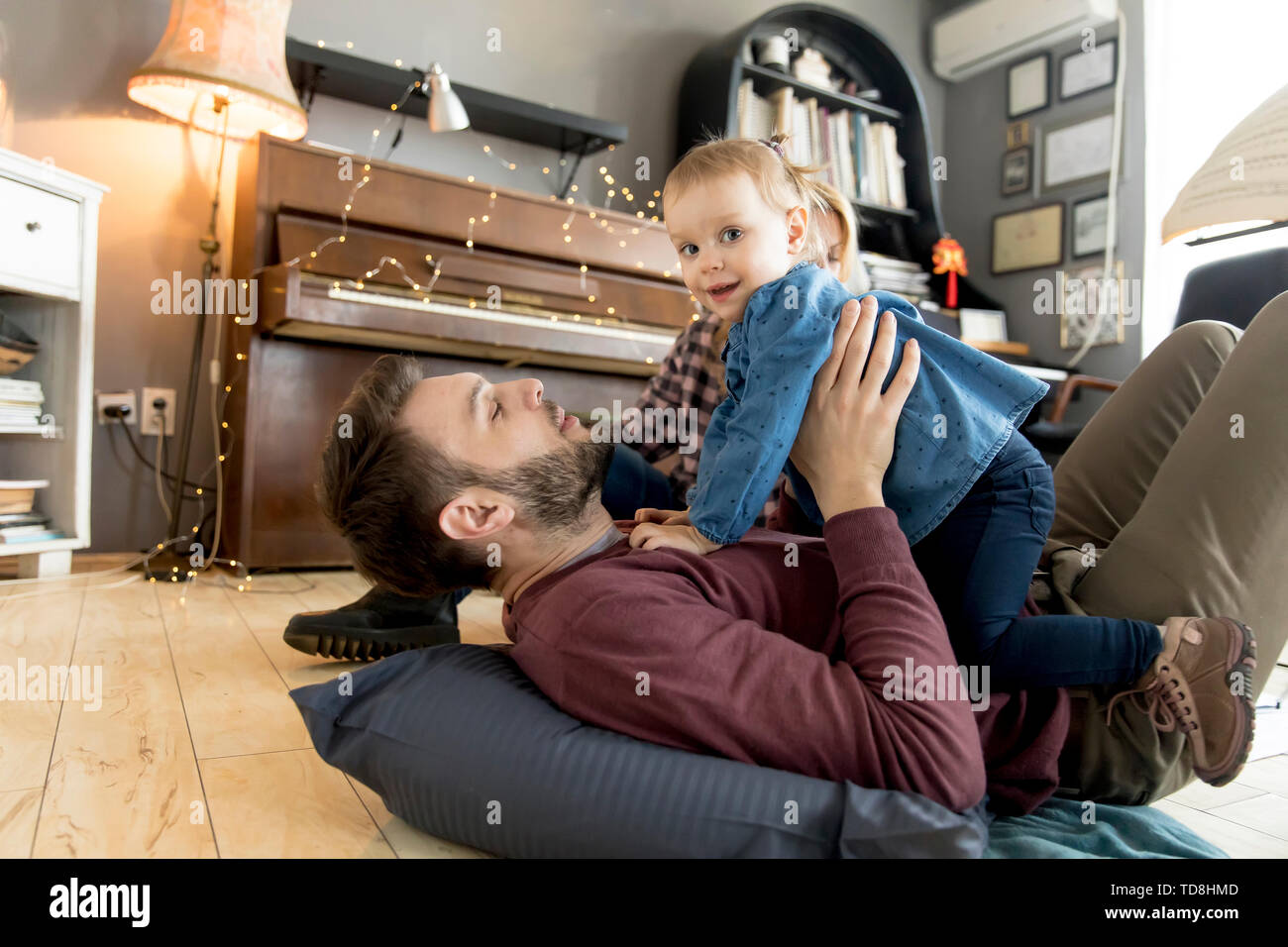 Happy young family with cute girl playing on the floor at rustic room - Stock Image