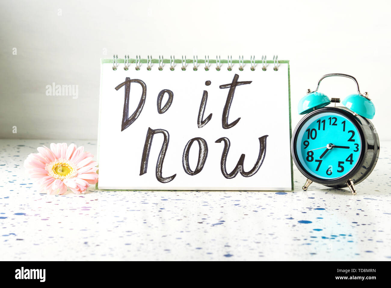 Do it now inspirational quote. Self motivation concept. Call to action. Open note pad and alarm clock. - Stock Image