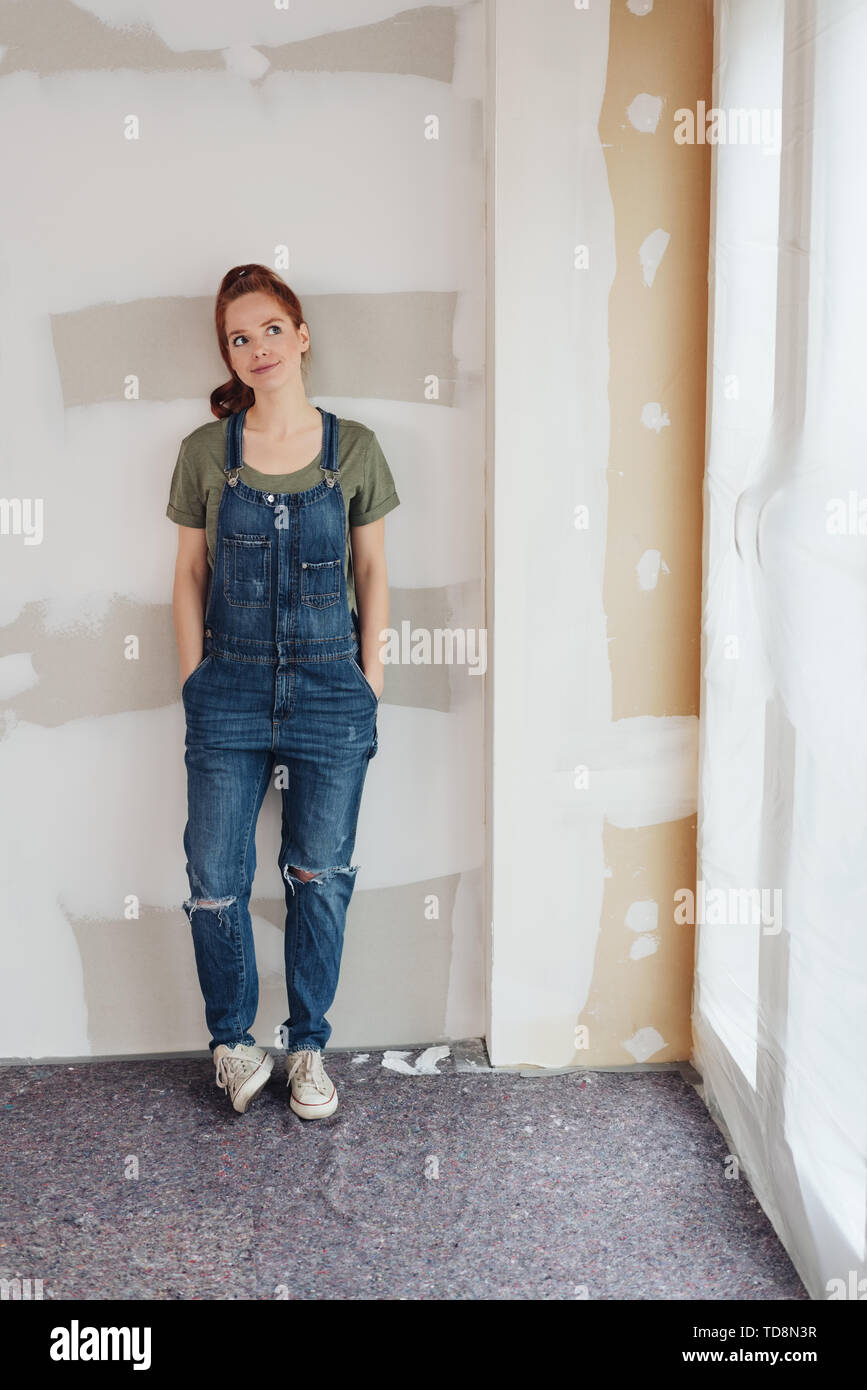 Dubious young woman standing contemplating her DIY renovations to her home in denim dungarees leaning against an unpainted wall - Stock Image
