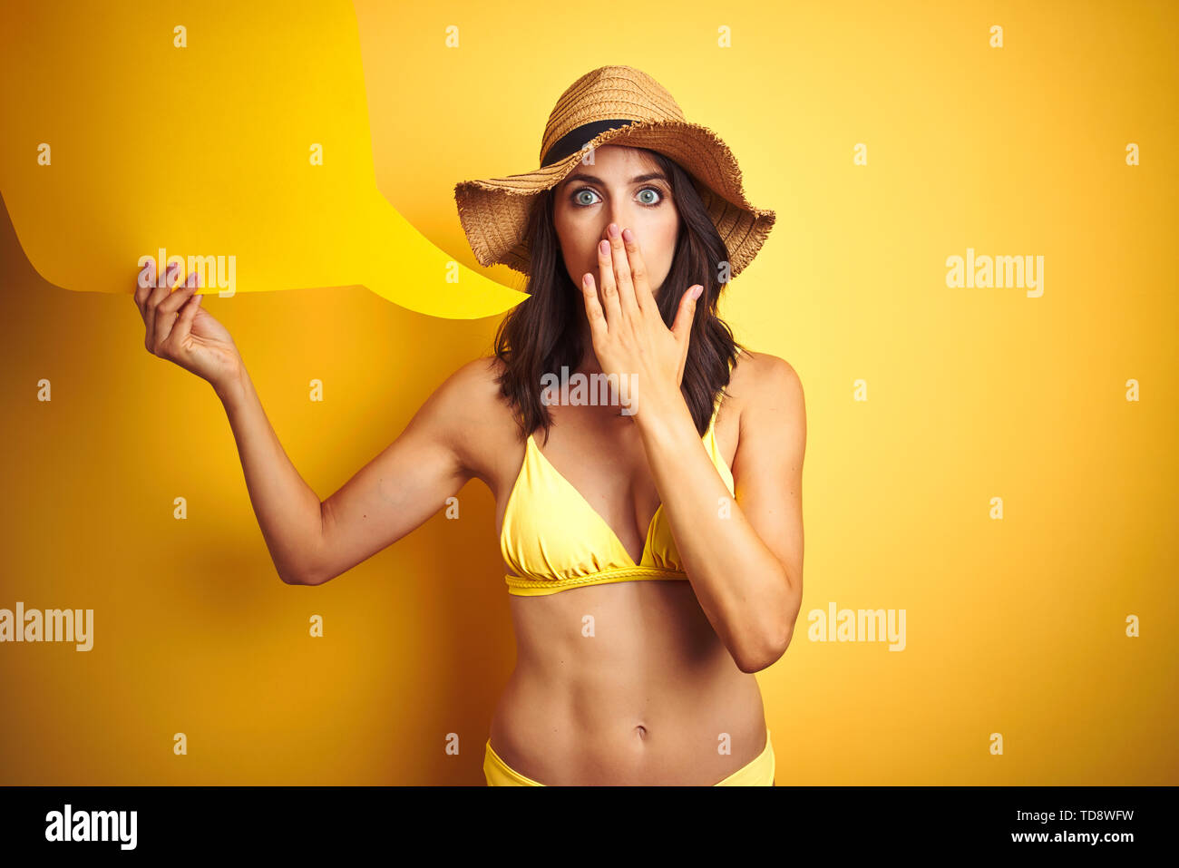Beautiful woman wearing yellow bikini and holding talking balloon over isolated yellow background cover mouth with hand shocked with shame for mistake - Stock Image