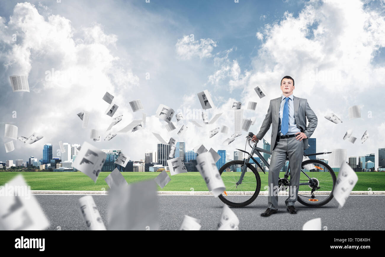 Man wearing business suit standing on road with bike. Businessman with bicycle under falling paper documents. Business information analysis. Outdoors  - Stock Image