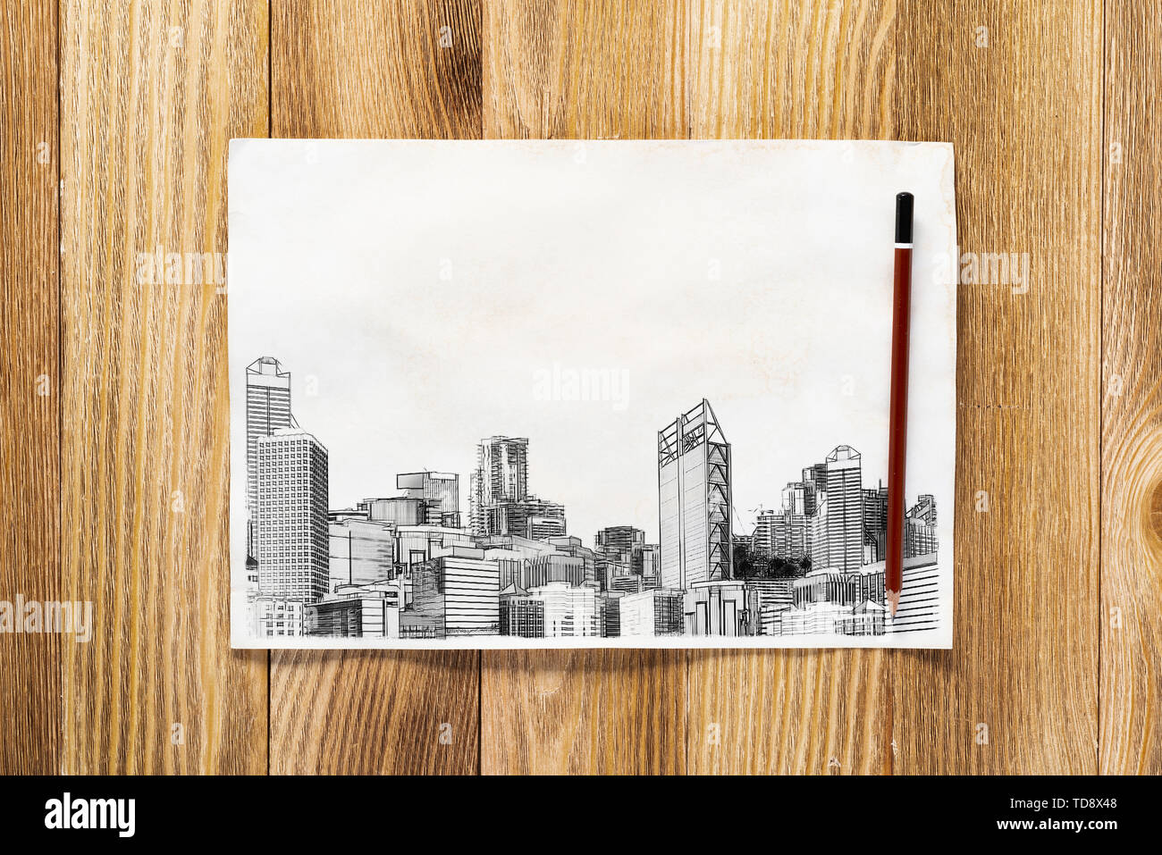 Big city skyline pencil draw. Modern downtown landscape with high skyscrapers sketch on wooden surface. Paper and pencil on textured natural wooden ba - Stock Image