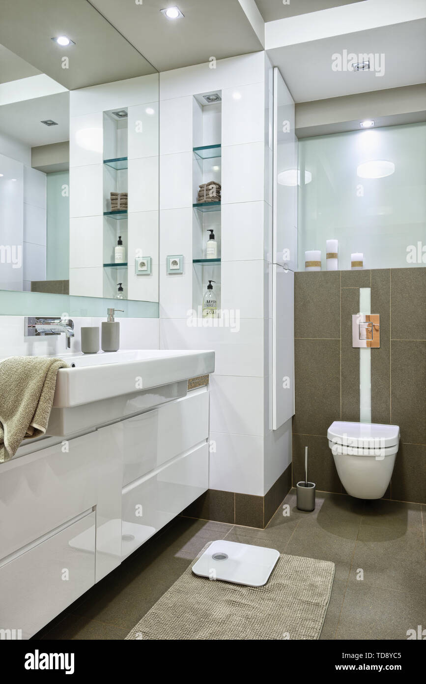 Glass shelves next to wall mirror and large washbasin in modern bathroom   UK & IRISH USE ONLY - Stock Image