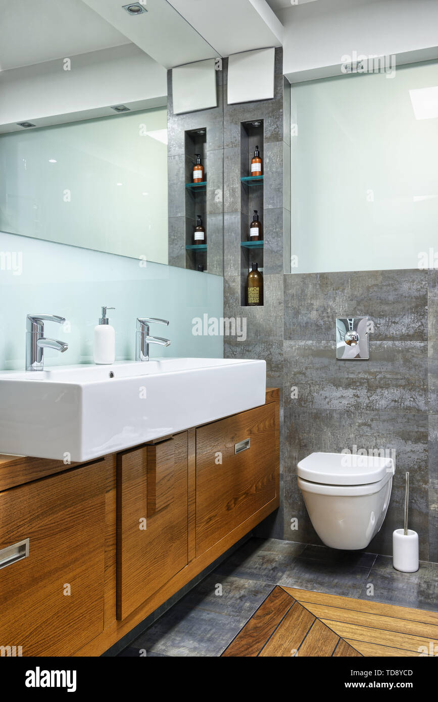Glass shelves next to wall mirror and large double washbasin in modern bathroom   UK & IRISH USE ONLY - Stock Image