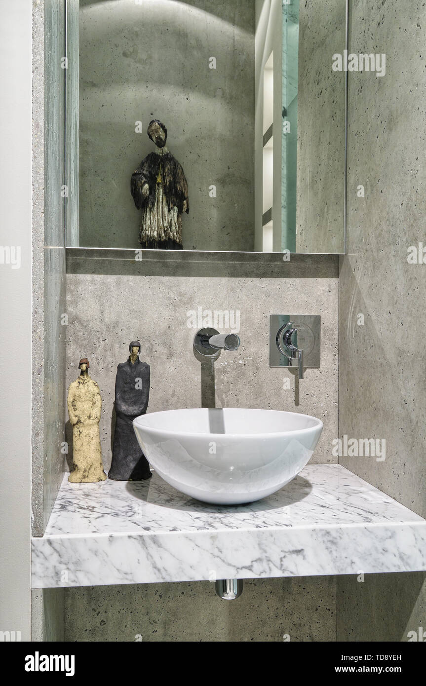 Vintage sculptures next to sink on marble countertop in modern eclectic bathroom UK & IRISH USE ONLY Stock Photo