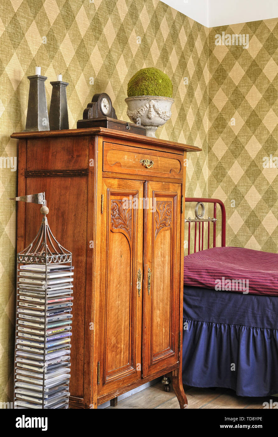 Antique cabinet on side of red metal bed in retro style teen boy bedroom    UK AND IRISH RIGHTS ONLY - Stock Image