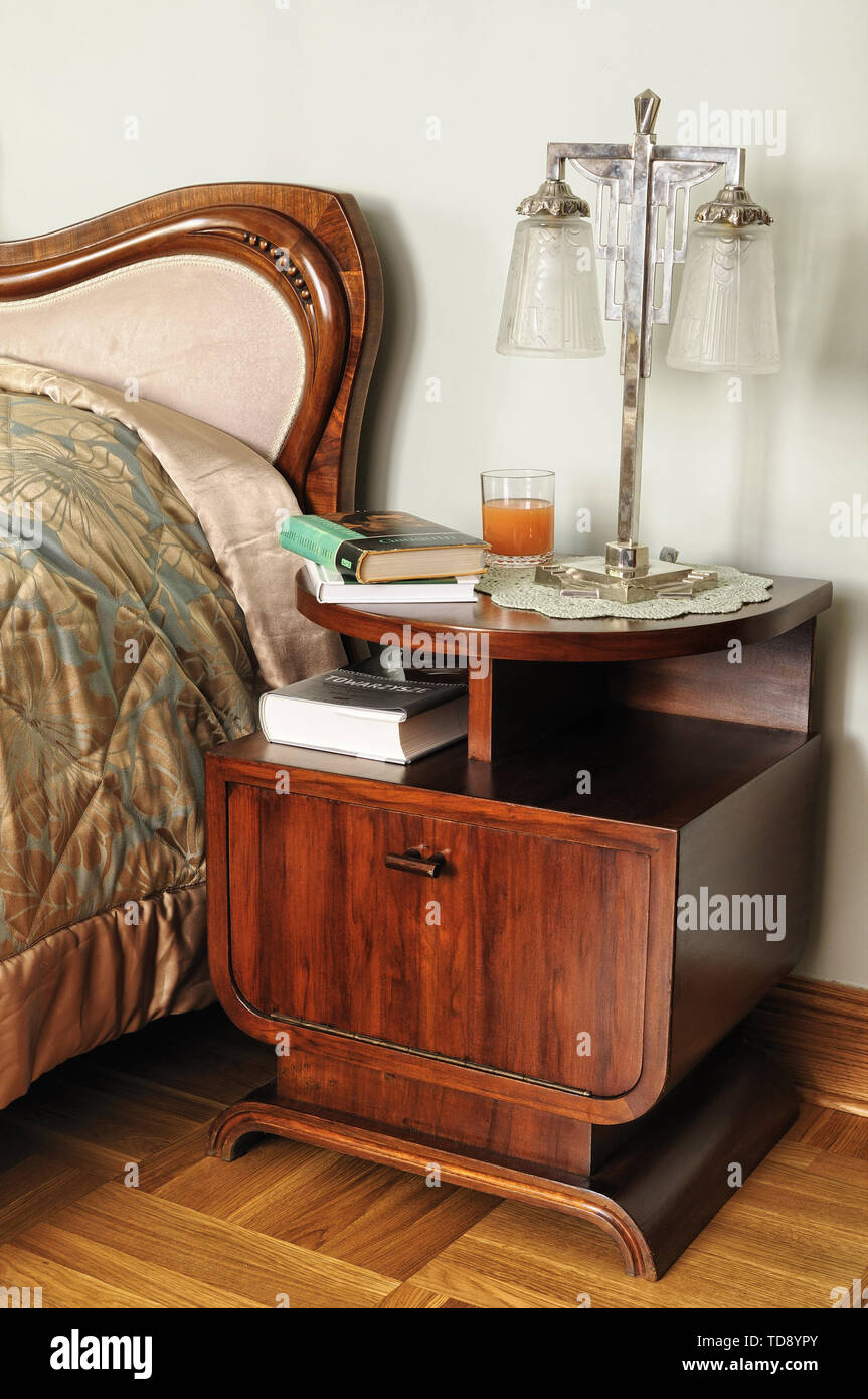 Wooden Art Deco Side Table Next To Comfortable Bed In Retro