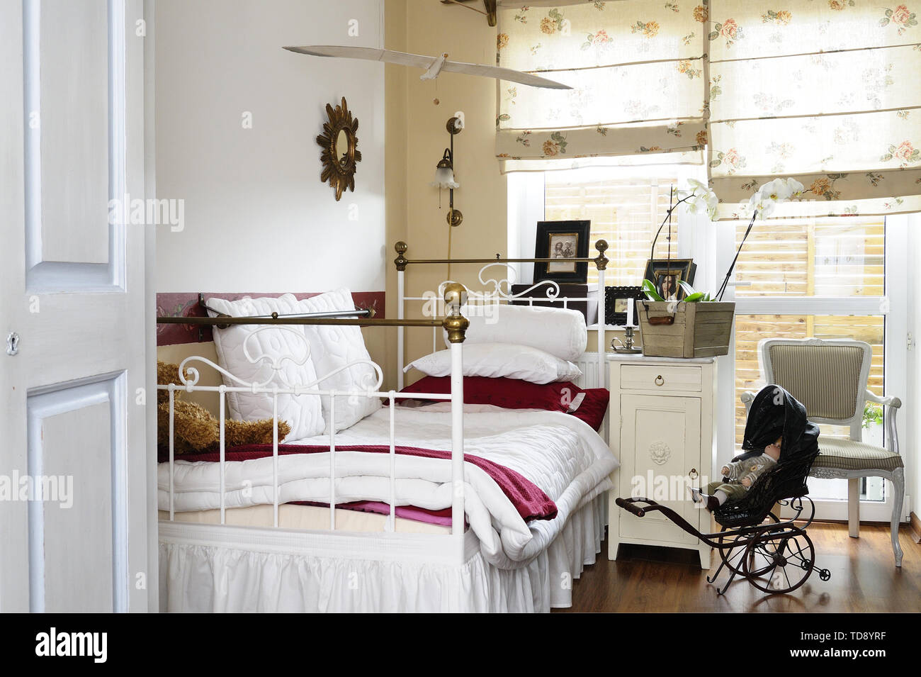 Black doll stroller next to rustic metal bed in teen girl bedroom   UK & IRISH USE ONLY - Stock Image
