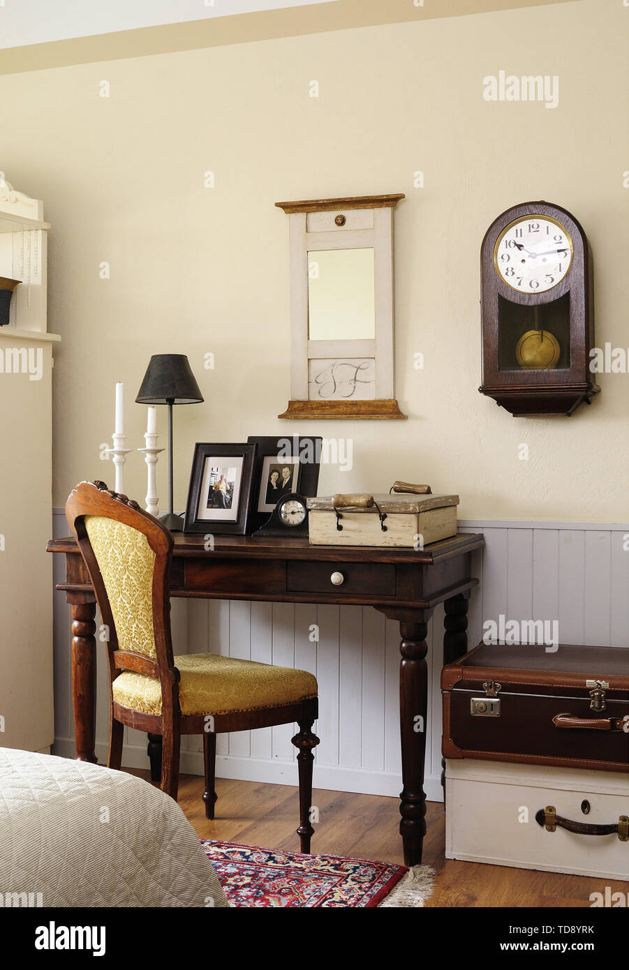 Framed family pictures and table lamp on brown side table in bedroom   UK & IRISH USE ONLY - Stock Image