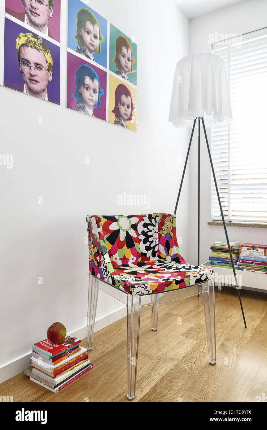 Designer chair and lamp next to Andy Warhol inspired pop art family portraits on bedroom wall   UK & IRISH USE ONLY - Stock Image