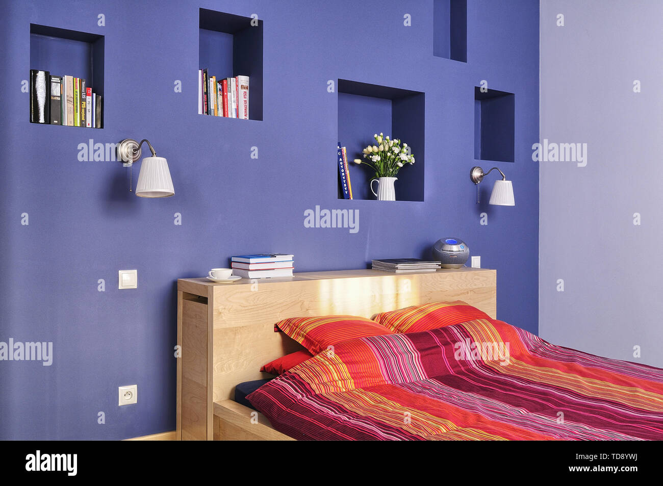 Recessed wall shelves above double bed with striped pattern bed linen in modern bedroom    UK AND IRISH RIGHTS ONLY - Stock Image