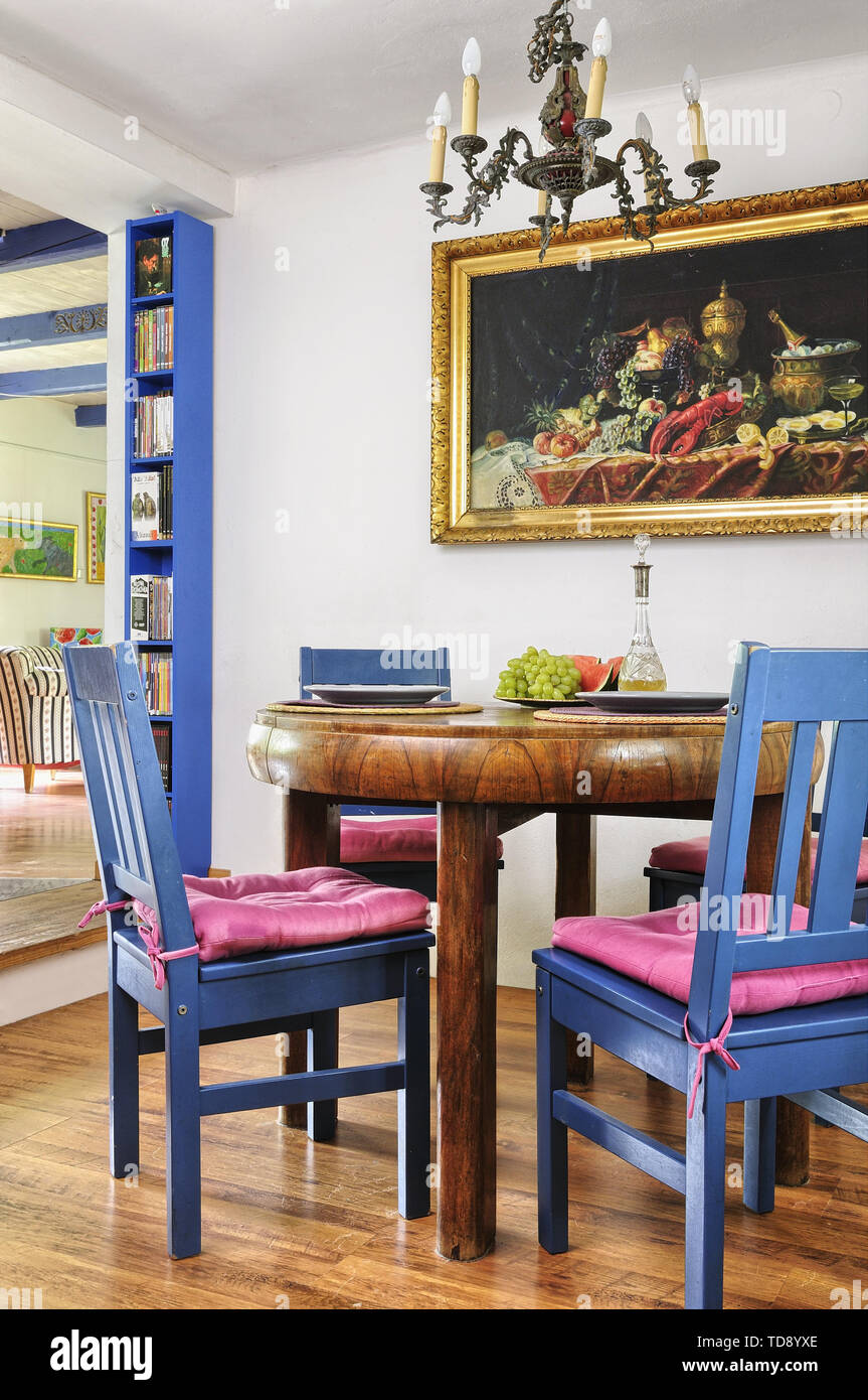 Round Wooden Dining Table With Blue Chairs In Dining Room Uk
