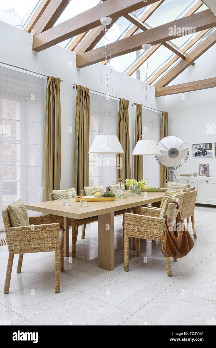 Dining room with dining table and wicker chairs in orangery    UK AND IRISH RIGHTS ONLY - Stock Image
