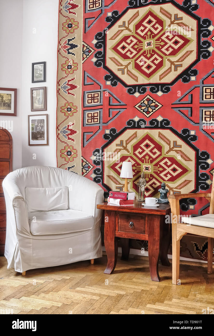 Two armchairs and oriental coffee table next to decorative rug on wall in living room    UK AND IRISH RIGHTS ONLY - Stock Image