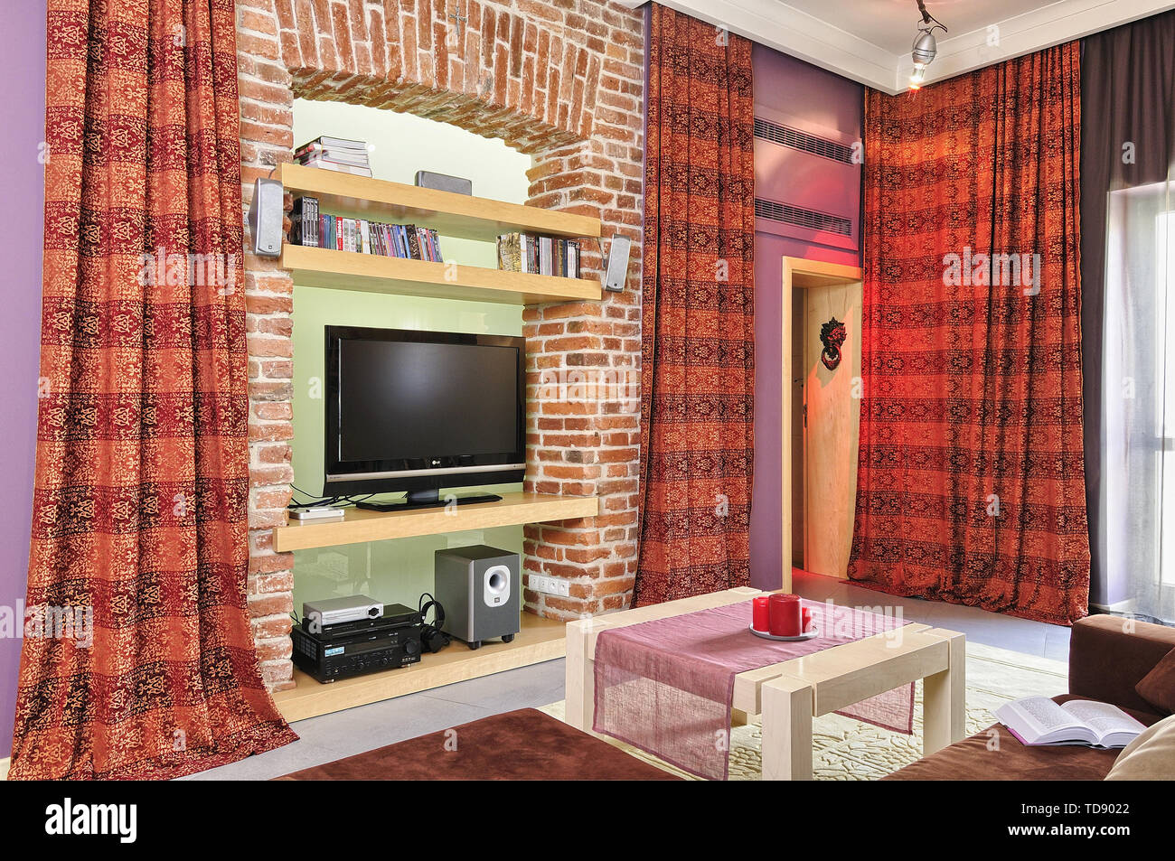 TV and audio video equipment on recessed brick wall shelves in modern living room    UK AND IRISH RIGHTS ONLY - Stock Image