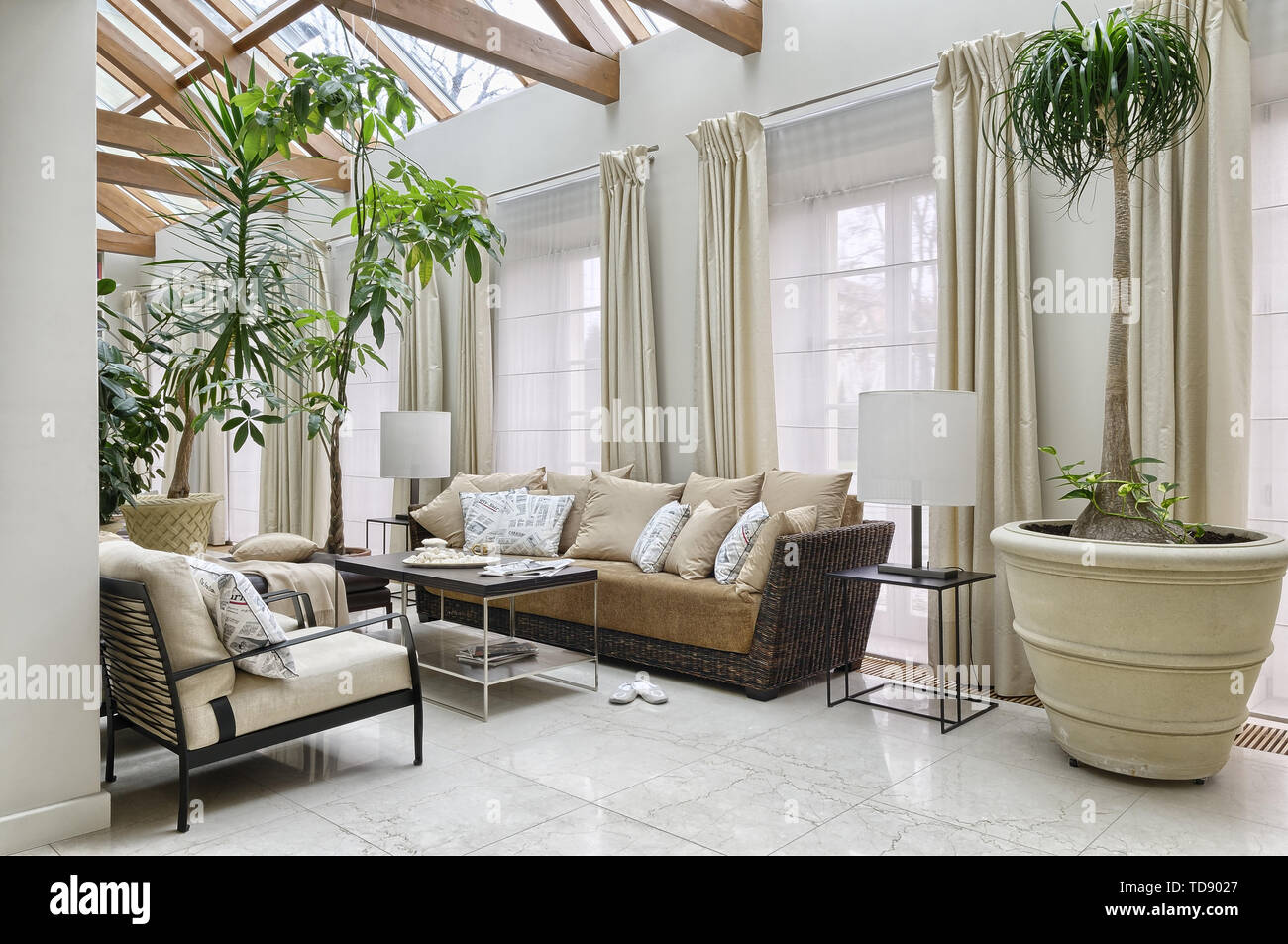 Meringues and tea on coffee table with chrome legs in front of Gervasoni rattan sofa with pillows in orangery    UK AND IRISH RIGHTS ONLY - Stock Image