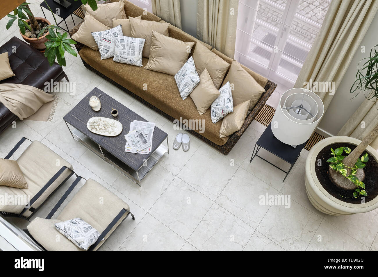 Meringues and tea on coffee table with chrome legs in front of Gervasoni rattan sofa with pillows and leather ottoman in orangery    UK AND IRISH RIGH - Stock Image