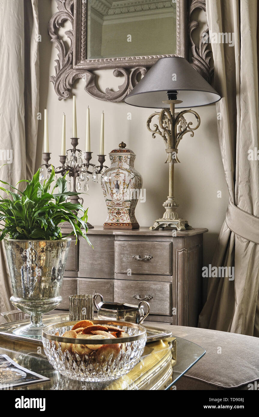 Glass Bowl And Silver Tray On Glass Topped Coffee Table In Living