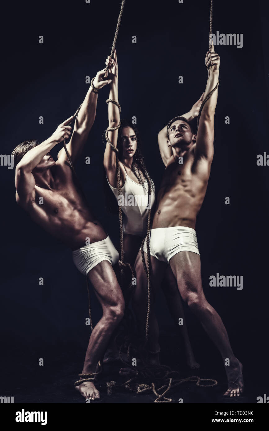 Young beautiful girl doing gymnastic isolated on black background with twins men - Stock Image