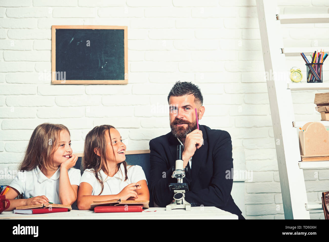 Teacher man experiment science with girls. Back to school and home schooling. Biology lesson and study at laboratory with microscope. School time of s - Stock Image