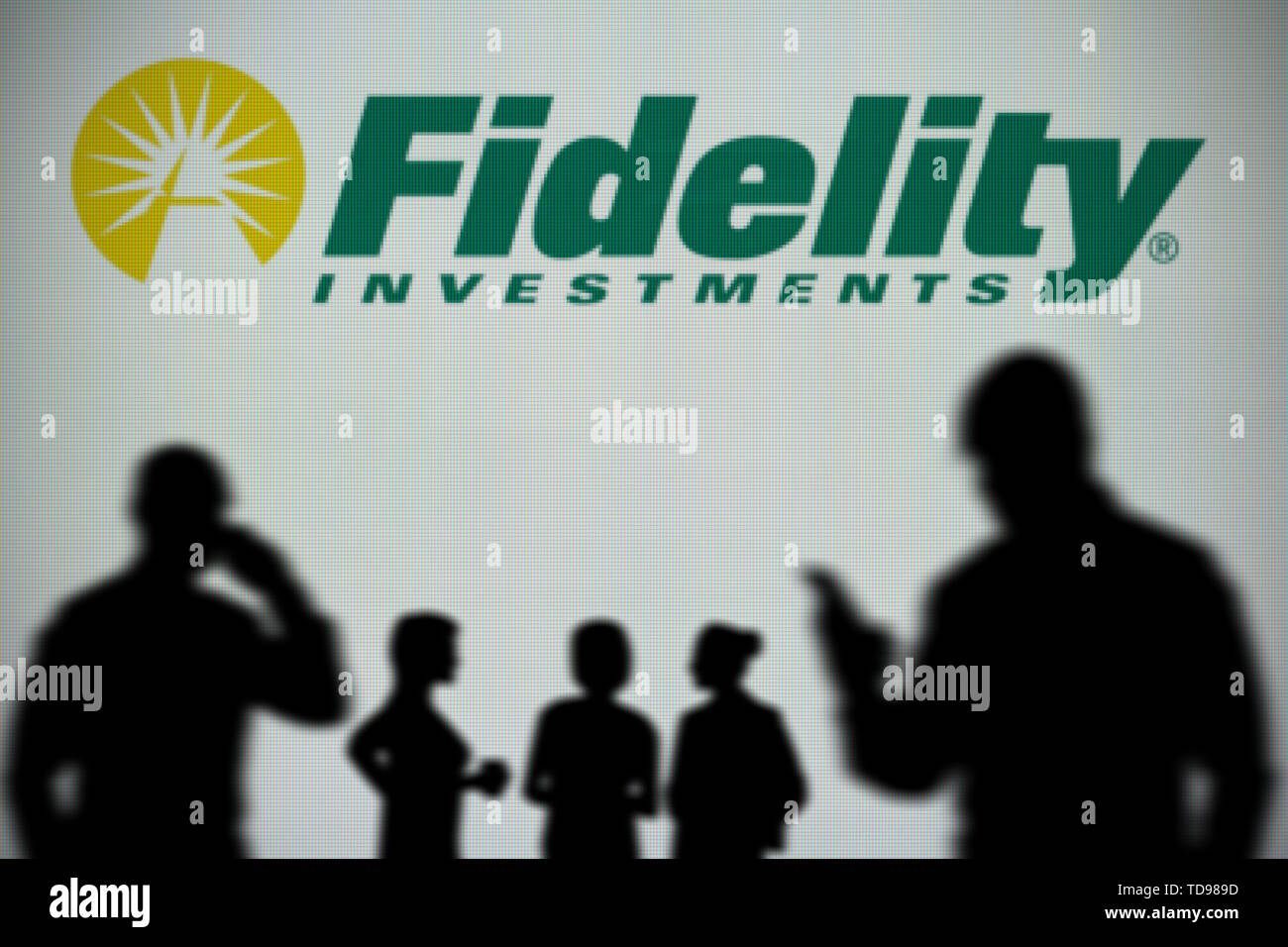 The Fidelity Investments logo is seen on an LED screen in the background while a silhouetted person uses a smartphone (Editorial use only) - Stock Image