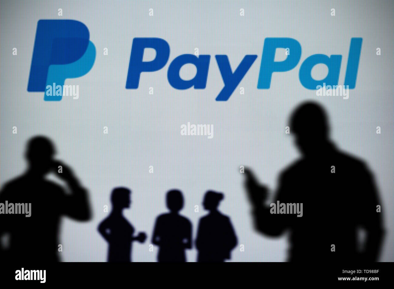 The PayPal logo is seen on an LED screen in the background while a silhouetted person uses a smartphone in the foreground (Editorial use only) - Stock Image
