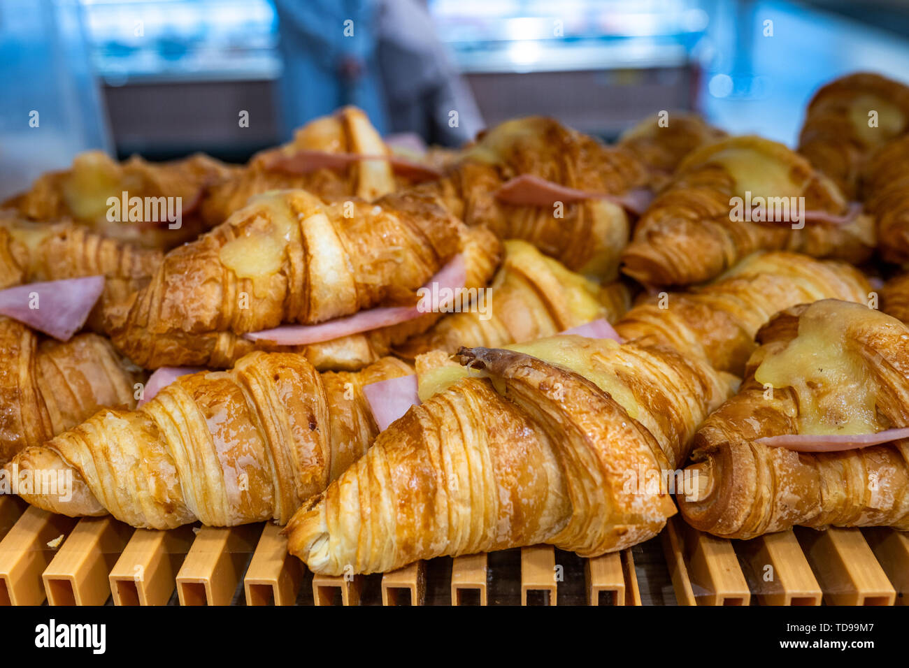 Croissant with melted cheese and ham selling at pastry shop - Stock Image