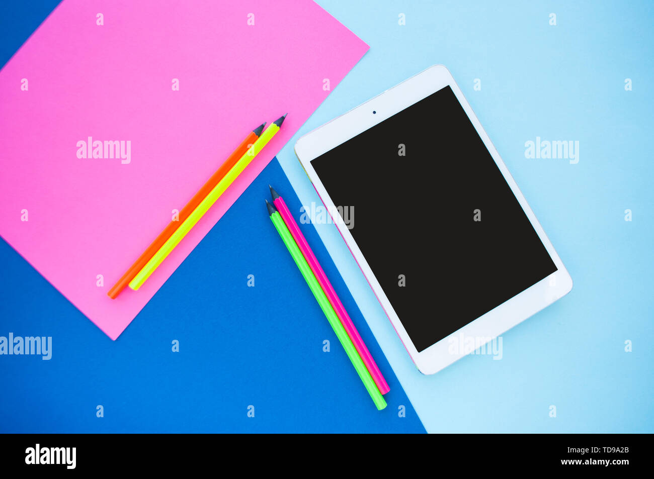 Colorful paper, neon pencils and tablet on blue and pink background with text space. Back to school concept. Stock Photo