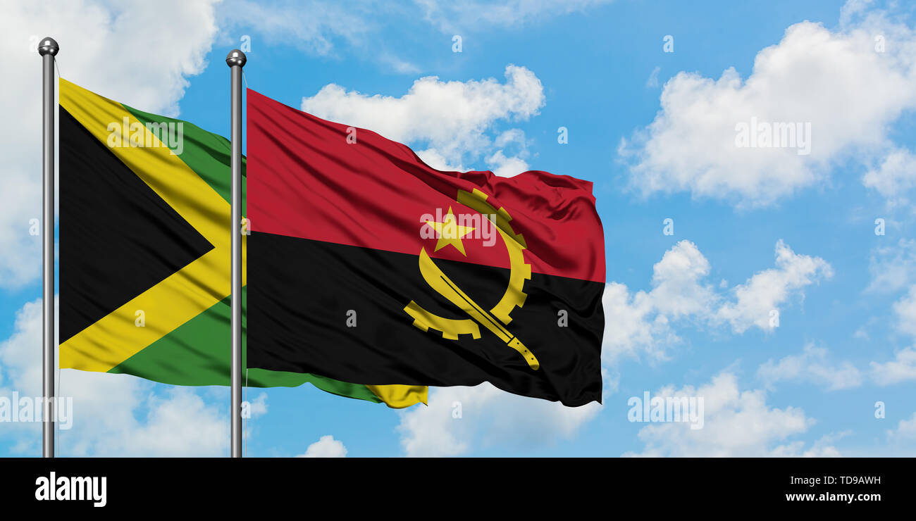 Jamaica and Angola flag waving in the wind against white cloudy blue sky together. Diplomacy concept, international relations. - Stock Image