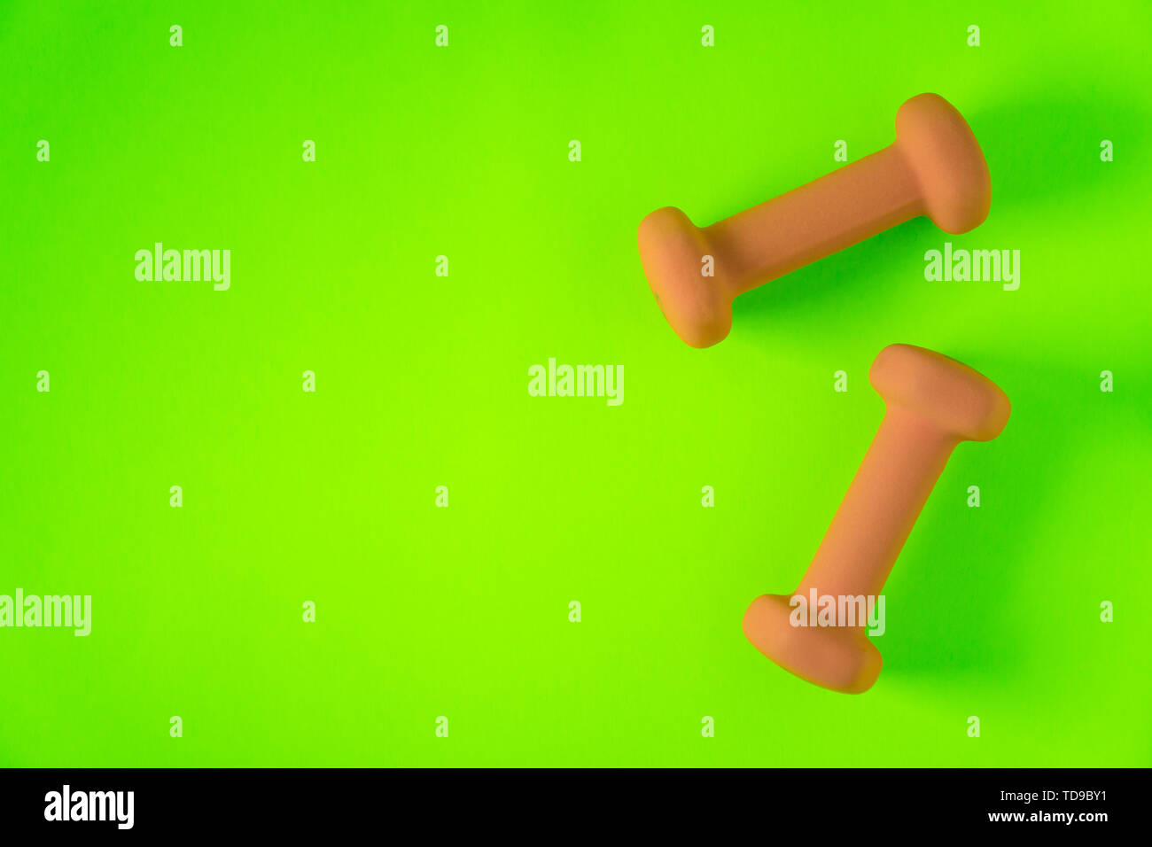 Fitness equipment with womens yellow orange weights/ dumbbells isolated on a neon lime green background with copyspace (aka empty text space). - Stock Image