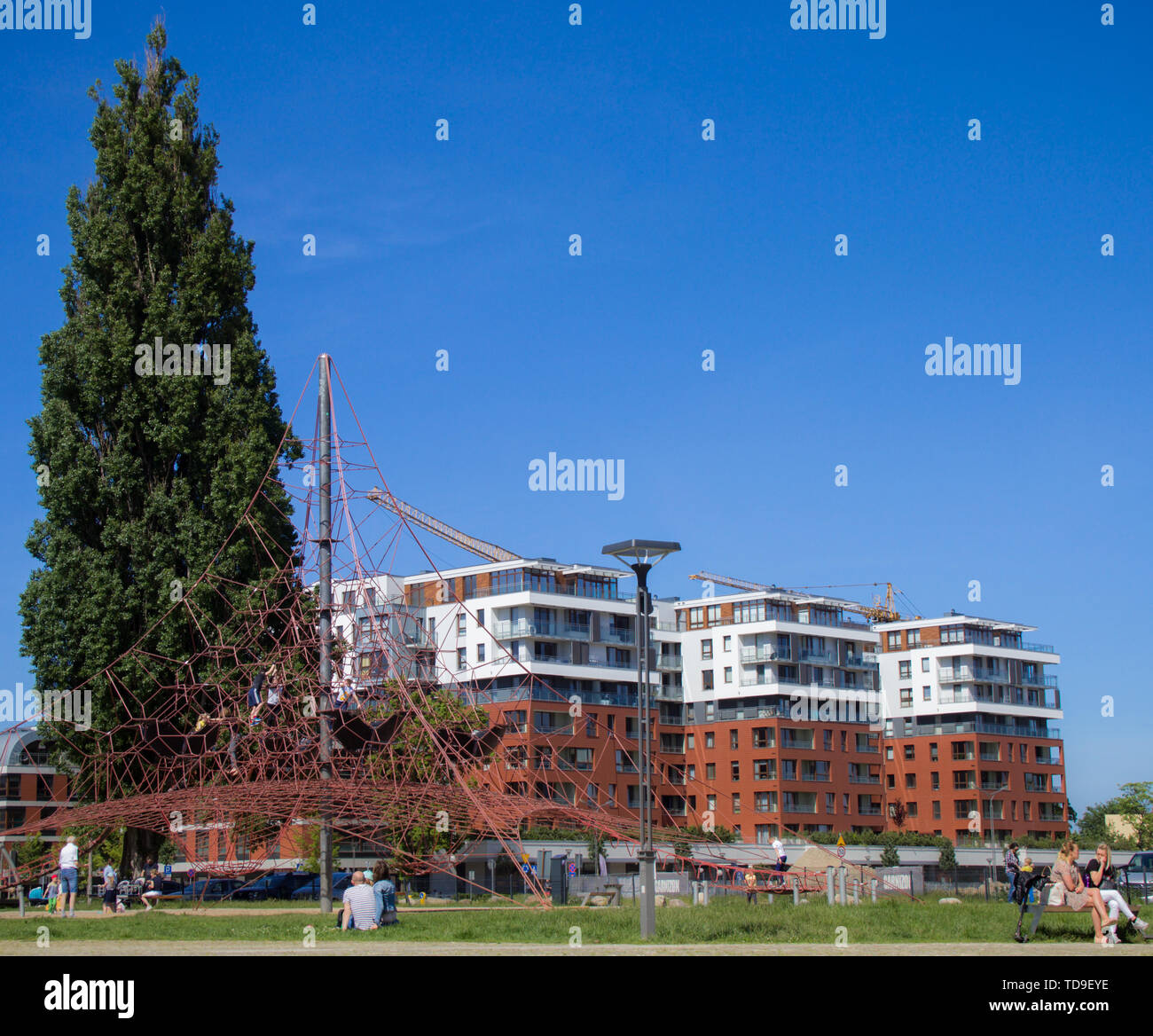 Gdansk Wrzeszcz, Poland - June 2, 2019: People relaxing on a sunny day in Garnizon with newly built houses in the background. Garnizon is a fashionabl - Stock Image