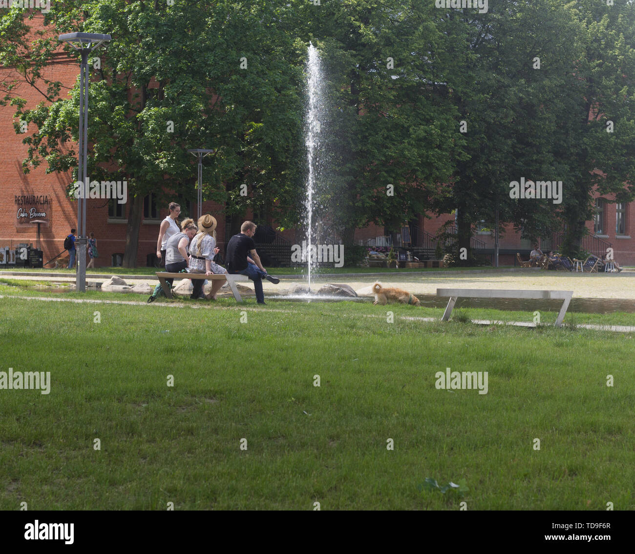 Gdansk Wrzeszcz, Poland - June 8, 2019: Family spends time together near the fountain in a recently gentrified district Garnizon. - Stock Image