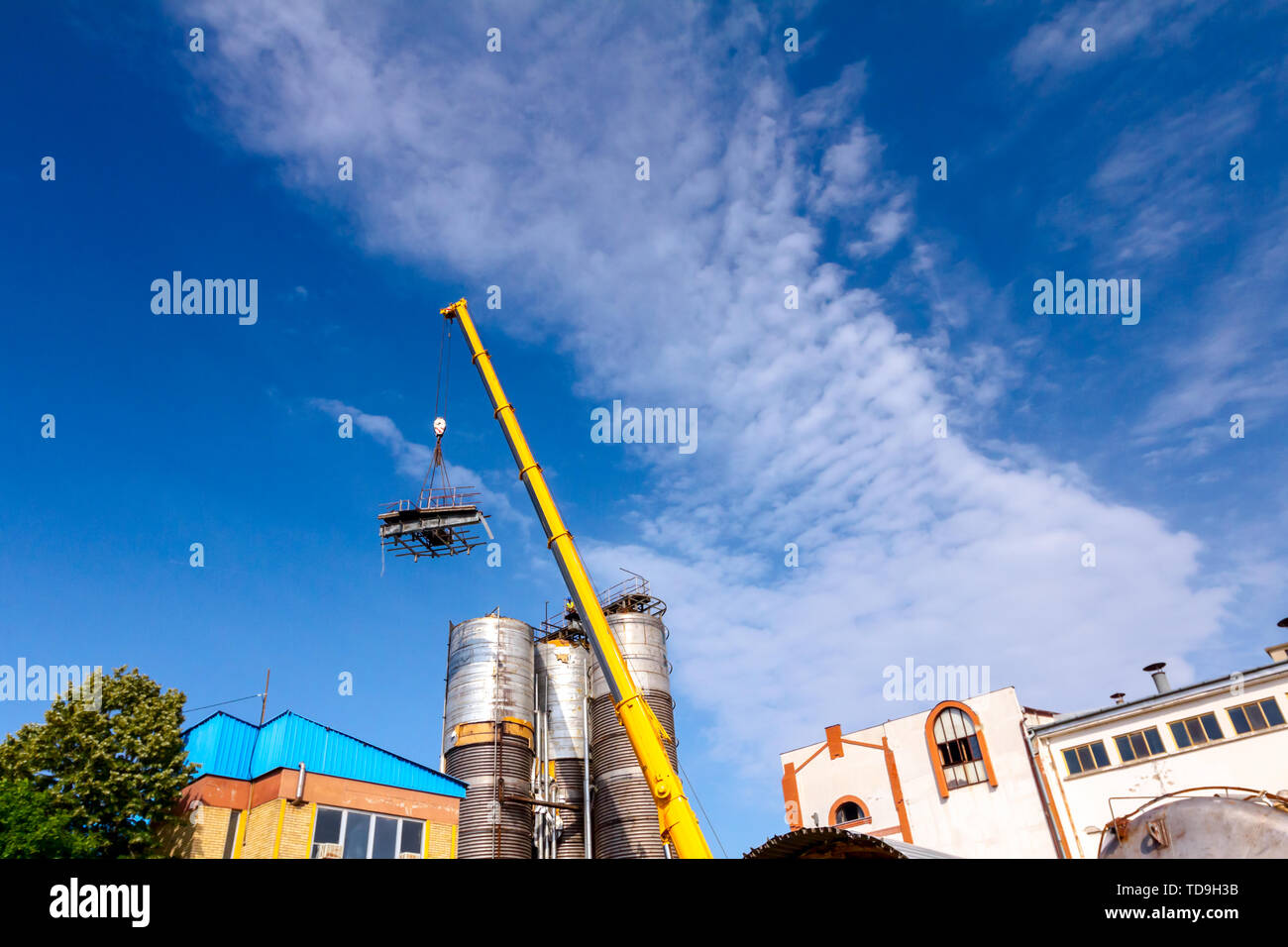 Crane is bringing down part of heavy metal construction in industrial complex. - Stock Image