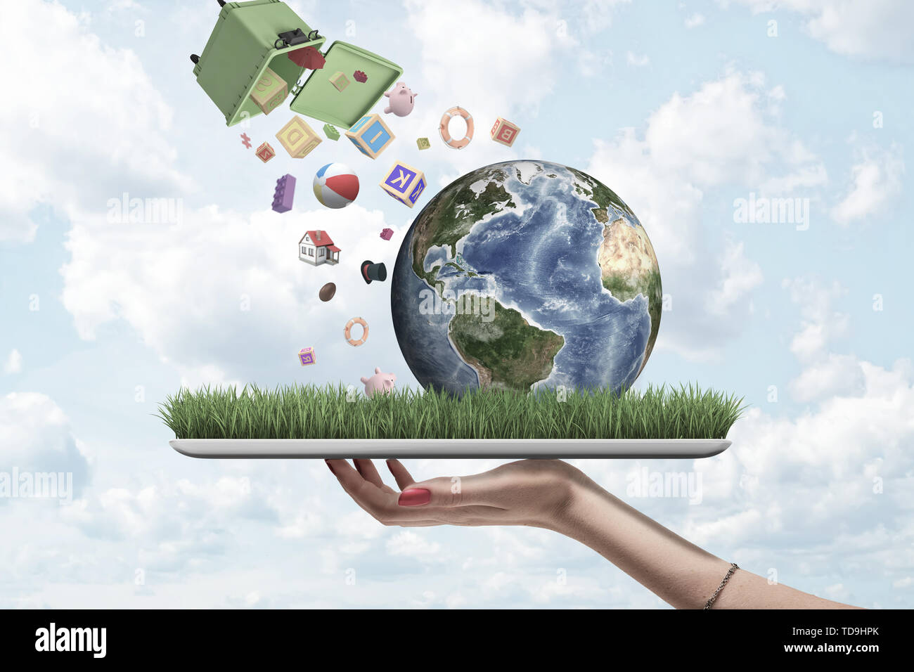 Hand holding digital tablet with grass growing on screen and little Earth on it, and dumpster toppled over in air from which a lot of objects are Stock Photo
