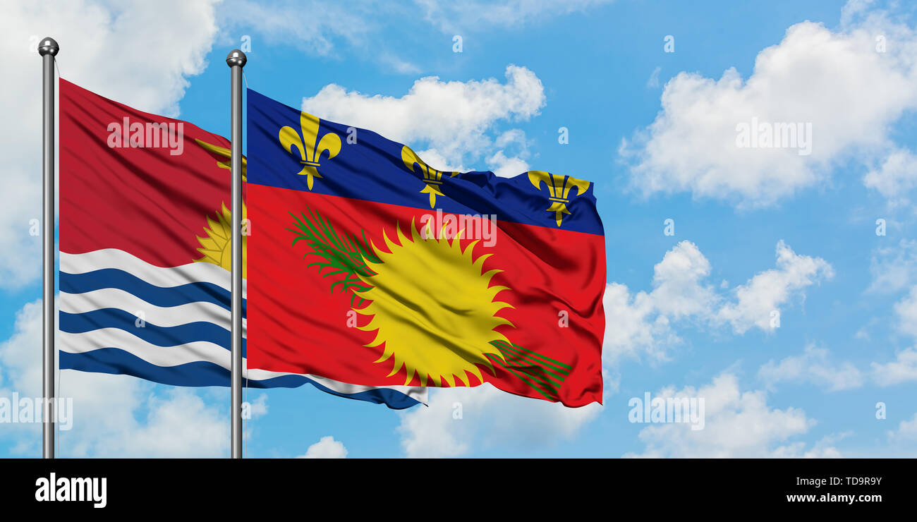 Kiribati and Guadeloupe flag waving in the wind against white cloudy blue sky together. Diplomacy concept, international relations. - Stock Image