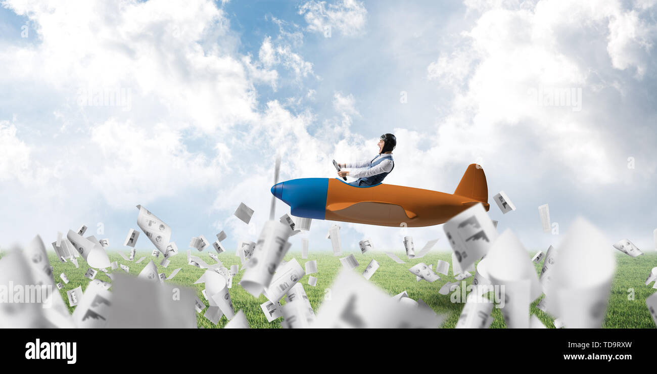 Businessman in aviator hat and goggles driving propeller plane above green field. Papers falling down on background of blue sky with clouds. Funny man - Stock Image