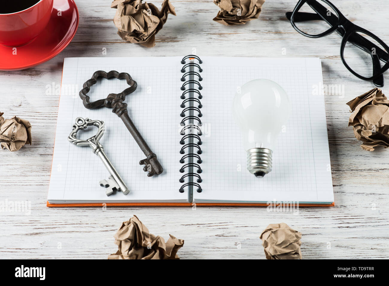 Top view of modern creative workplace with keys and lightbulb on notepad, crumpled paper balls and coffee on wooden table. Concept of finding of outst - Stock Image