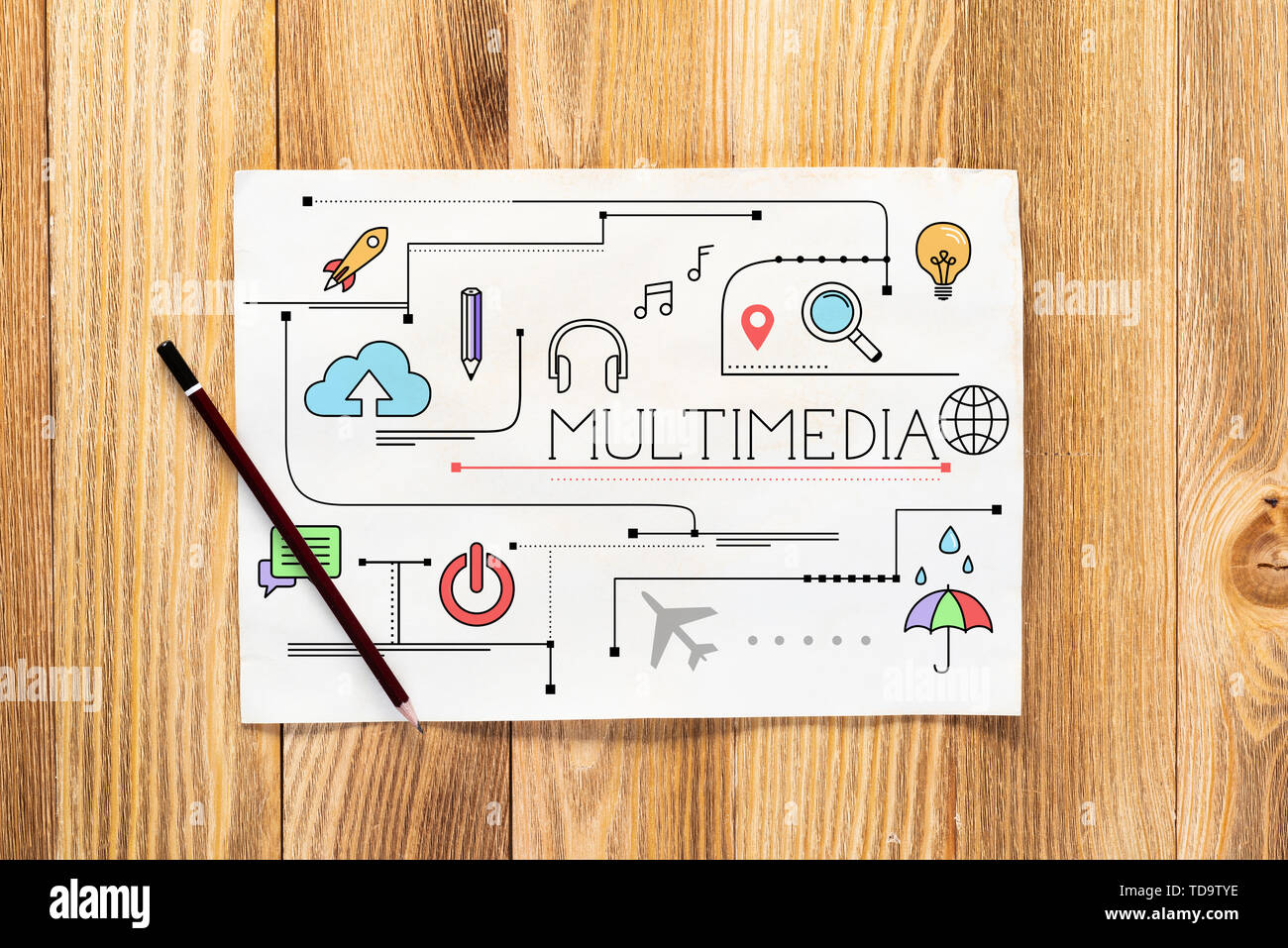 Multimedia content pencil hand drawn with group of social media doodles. Top view of workplace with paper and pencil lying on wooden desk. Commercial  - Stock Image