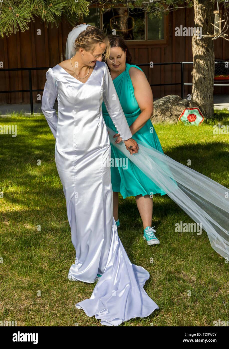 Outdoor photo of bridesmaid & bride; Congressional Church; Buena Vista; Colorado; USA - Stock Image