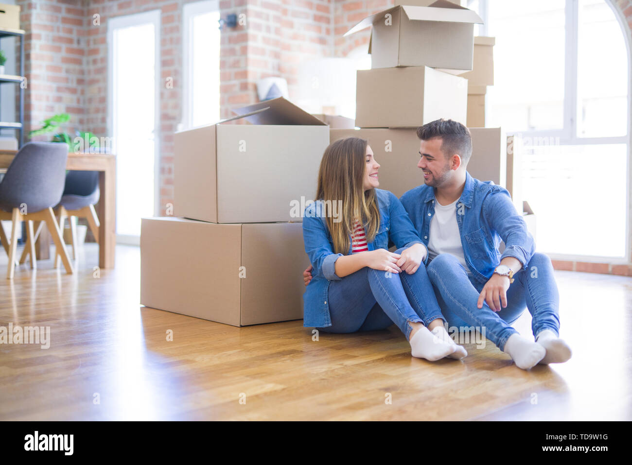 Young beautiful couple in love moving to new home, sitting on the floor very happy and cheerful for new apartment around cardboard boxes - Stock Image